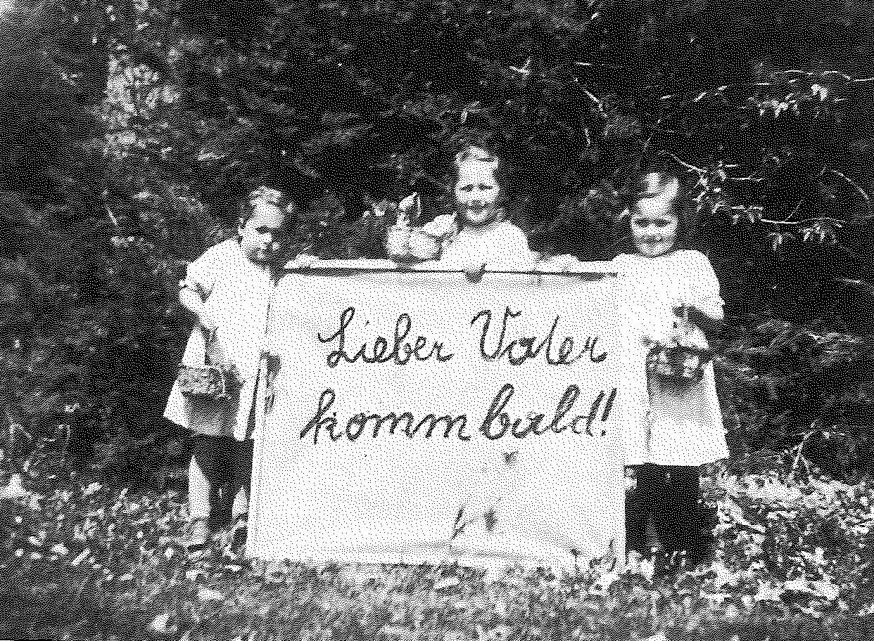 """Easter 1943: Franz Jagerstatter's daughters; Loisi, Rosi, and Maria, holding a sign that reads, """"Dear Father, come [home] soon."""" Franz was in jail in Linz and was later executed./Styria Verlag. Used with permission"""